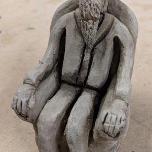 Sculpture of a man sitting in a chair