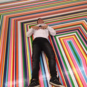 Young man lying on a colourful striped floor