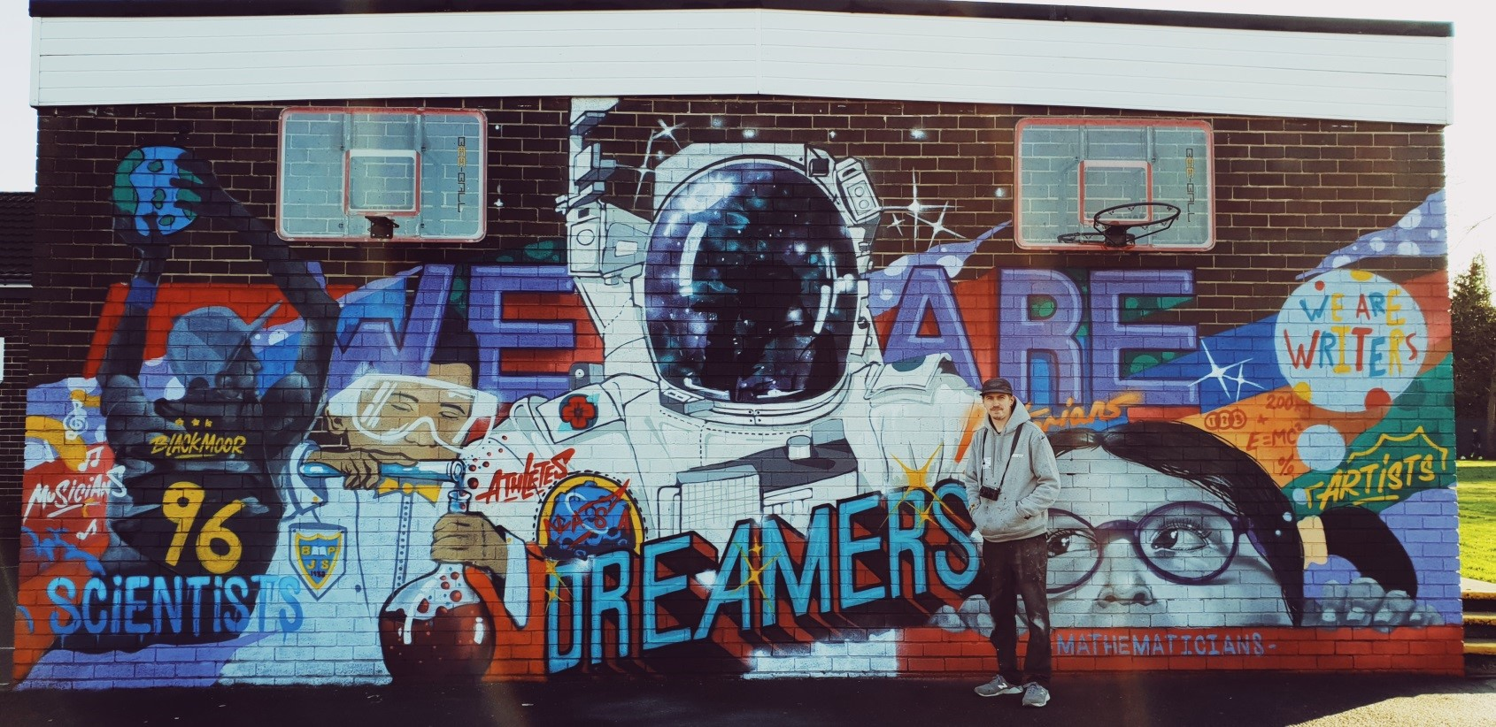 Mural on a wall of an astronaut, other figures and the words 'we are dreamers'