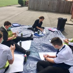 People sitting on the ground outside with paper and spray paint