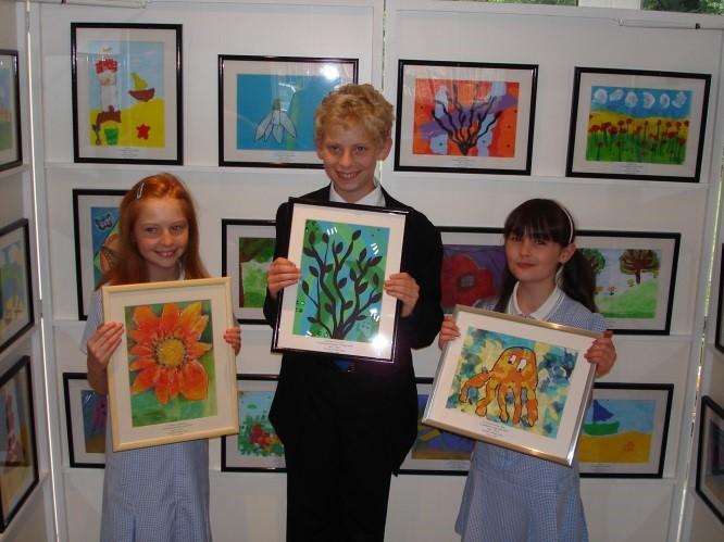 3 children holding up framed images of artwork